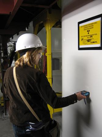 CNSC inspector  verifies radiation levels outside a dry storage container